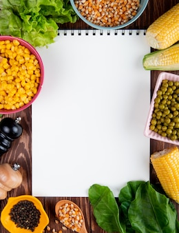 Vista superior del bloc de notas con semillas de maíz lechuga espinacas semillas de pimienta negra guisantes verdes con espacio de copia