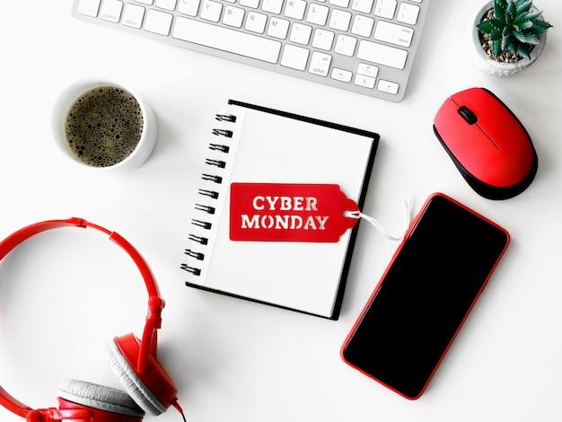Vista superior del bloc de notas con teléfono inteligente y auriculares para cyber monday