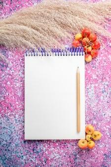 Vista superior del bloc de notas vacío con bolígrafo sobre superficie rosa claro