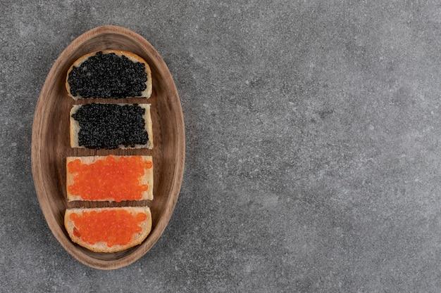 Vista superior de bocadillos de caviar rojo y negro.