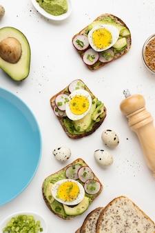 Vista superior de bocadillos con huevo y aguacate junto al plato