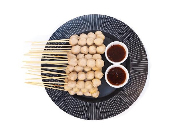 Vista superior de la bola de carne a la parrilla con tazas de salsa picante dulce en un plato negro aislado sobre fondo blanco.