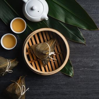 Vista superior de la bola de masa de arroz de zongzi para el festival del barco del dragón tradicional chino (festival de duanwu) sobre fondo de pizarra negro oscuro.