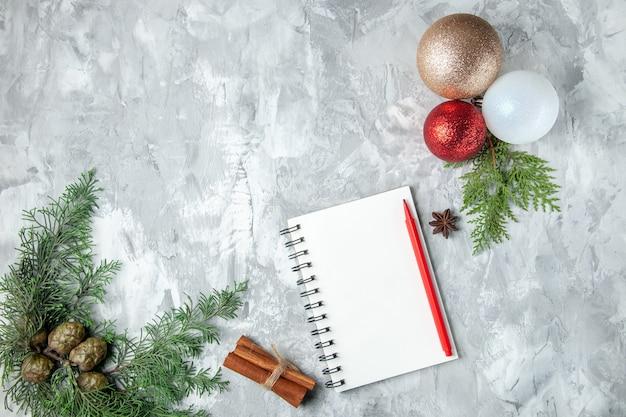Vista superior de bolas de árbol de navidad cuaderno lápiz palitos de canela en superficie gris