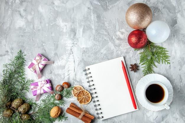 Vista superior de bolas de árbol de navidad cuaderno lápiz palitos de canela taza de té anís estrellado sobre fondo gris