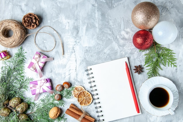 Vista superior bolas de árbol de navidad cuaderno lápiz palitos de canela taza de té hilo de paja sobre superficie gris