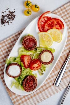 Vista superior de bolas fritas con champiñones y tomates