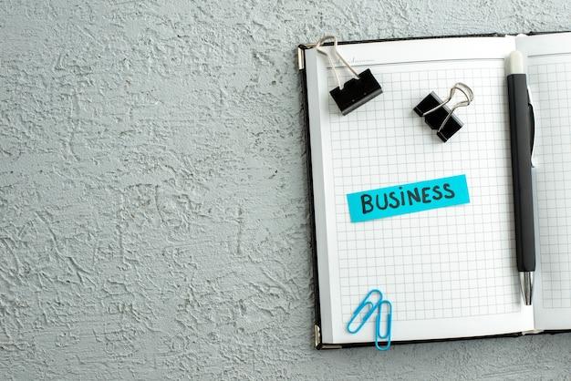 Vista superior del bolígrafo de negocios de color azul y cuaderno de espiral abierto sobre fondo de arena gris