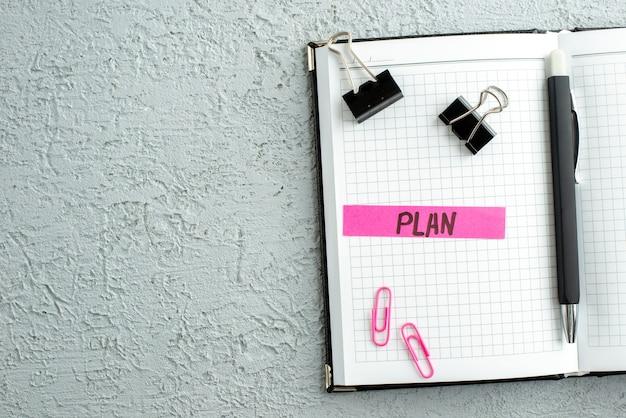 Vista superior del bolígrafo de plan de color rosa y cuaderno de espiral abierto sobre fondo de arena gris