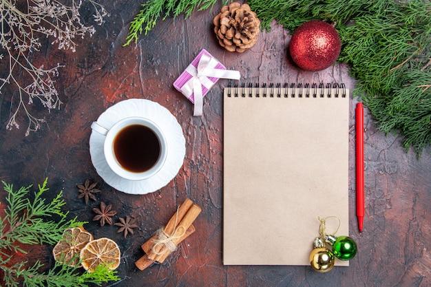 Vista superior bolígrafo rojo un cuaderno ramas de pino árbol de navidad juguetes de bolas palitos de canela una taza de té anís estrellado en la superficie de color rojo oscuro