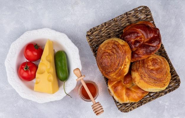 Vista superior de bollos frescos en bandeja de mimbre con verduras y queso en un plato blanco con miel sobre un fondo blanco.