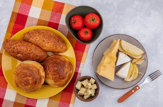 Vista superior de bollos frescos en una placa amarilla sobre un paño a cuadros con diferentes tipos de queso en una placa gris con tomates en un recipiente sobre un fondo blanco.
