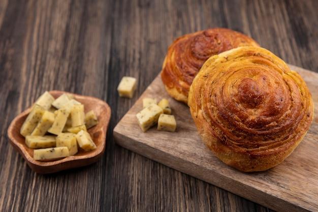 Vista superior de bollos suaves sobre una tabla de cocina de madera con rodajas de queso picado en un cuenco de madera sobre un fondo de madera