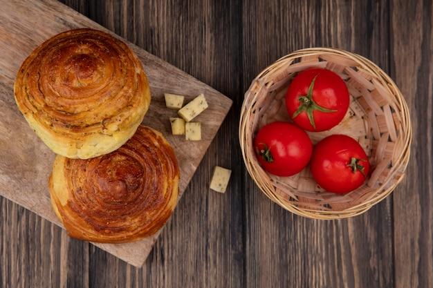 Vista superior de bollos en una tabla de cocina de madera con rodajas de queso y tomates picados en un cubo sobre un fondo de madera