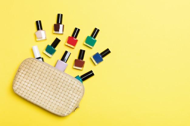 Vista superior de la bolsa de cosméticos con esmaltes de uñas coloridos caídos sobre fondo amarillo. concepto de uñas hermosas con espacio vacío para texto