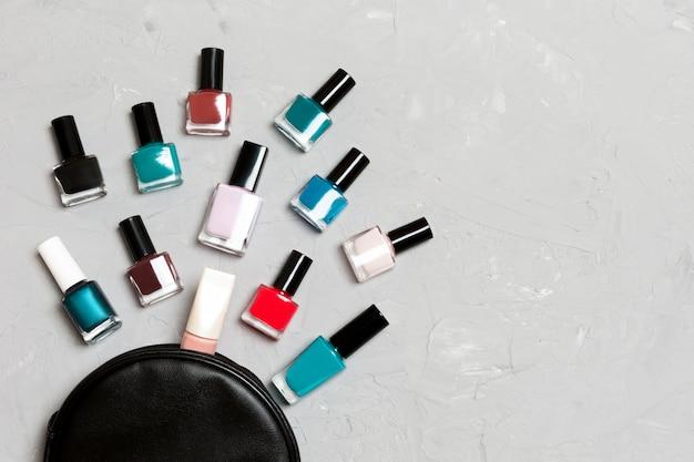 Vista superior de la bolsa de cosméticos con esmaltes de uñas coloridos caídos sobre fondo de cemento. concepto de uñas hermosas con espacio vacío para texto