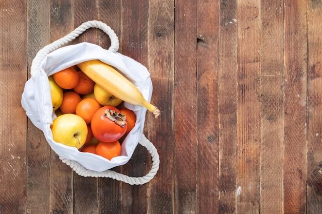 Vista superior de la bolsa de lino blanco ecológico de fruitson madura mesa de madera vieja.