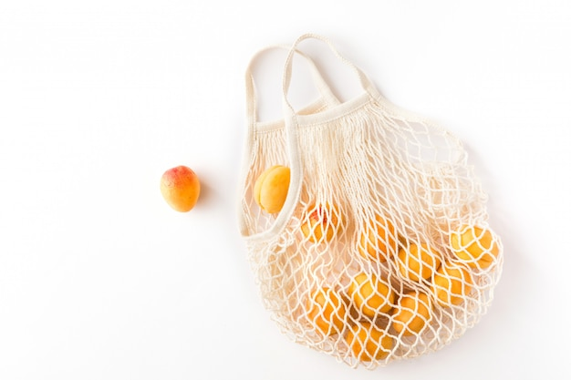 Vista superior de la bolsa de malla con frutas ecológicas orgánicas aisladas