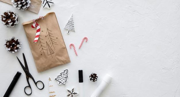Vista superior de la bolsa de papel navideña con tijeras y espacio de copia