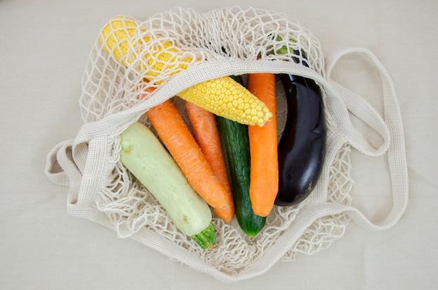 Vista superior bolsa de red de ganchillo con zanahorias y berenjenas