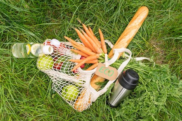 Vista superior bolsa reutilizable con comestibles sobre hierba