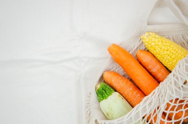 Vista superior bolsa con verduras sobre fondo blanco.