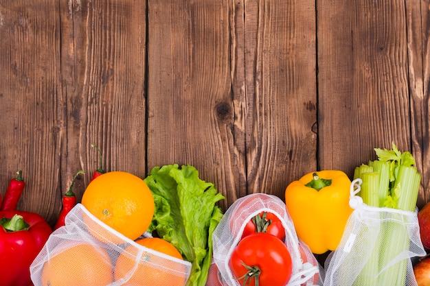 Vista superior de bolsas reutilizables en superficie de madera con frutas y verduras.