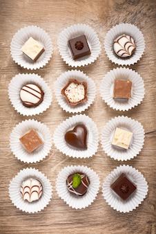 Vista superior de bombones de chocolate surtidos sobre madera
