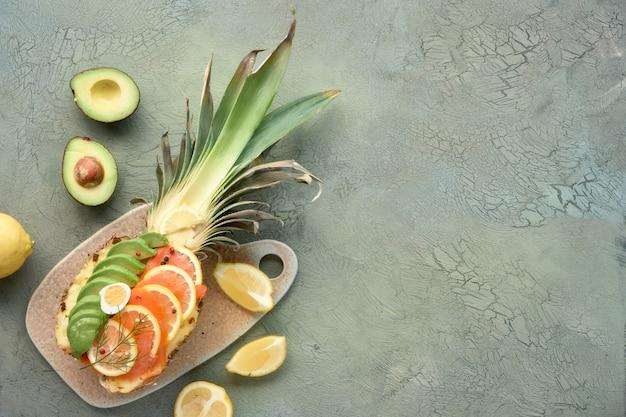 Vista superior en bote de piña con salmón ahumado, aguacate, limón y huevos de codorniz