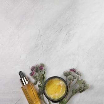 Vista superior de la botella de aceite esencial y mantequilla corporal sobre fondo de mármol
