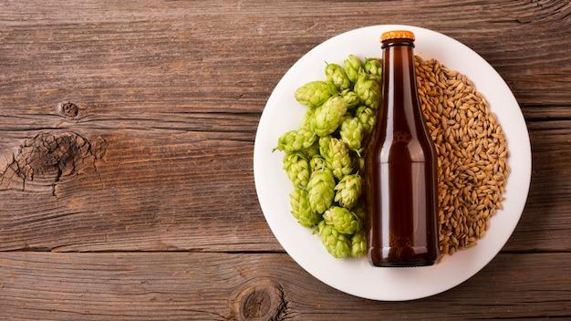 Vista superior botella de cerveza con ingredientes