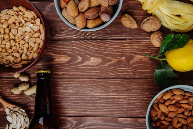 Vista superior de una botella de cerveza con una mezcla de bocadillos salados, maní, queso de almendras con limón sobre madera rústica con espacio de copia