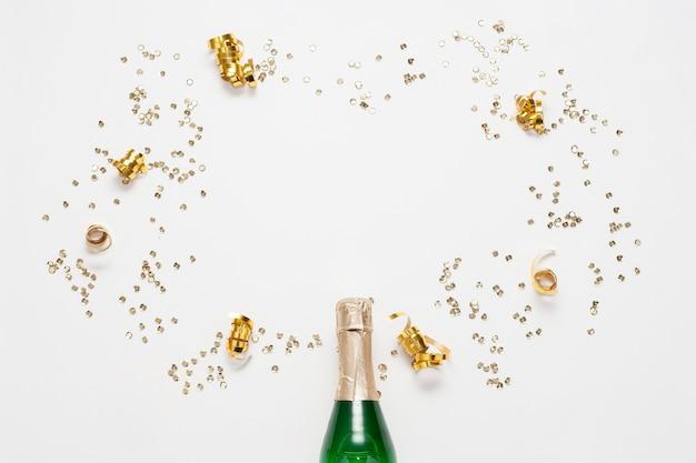 Vista superior botella de champagne con cintas doradas y confeti