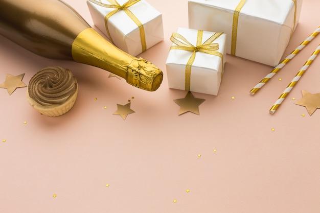 Vista superior botella de champagne con regalos
