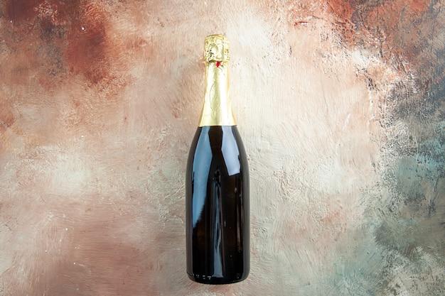 Vista superior botella de champán en color claro beber alcohol foto fiesta de año nuevo