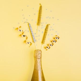 Vista superior botella de champán dorado y cintas con velas