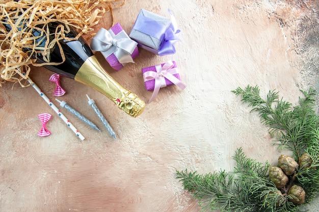 Vista superior botella de champán con pequeños regalos en color claro regalo alcohol foto fiesta de año nuevo