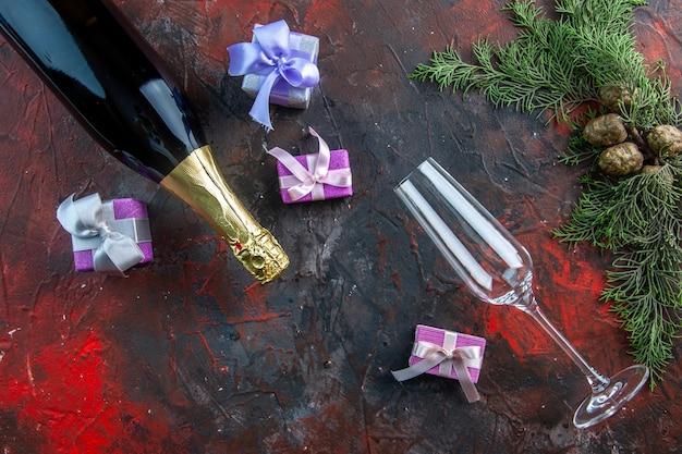 Vista superior de la botella de champán con pequeños regalos en color oscuro beber alcohol foto fiesta de año nuevo