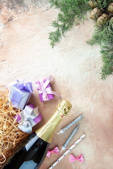 Vista superior de la botella de champán con pequeños regalos en la fiesta de fotos de alcohol de regalo de año nuevo claro