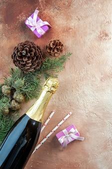 Vista superior de la botella de champán con pequeños regalos en la luz de navidad foto año nuevo regalo color alcohol