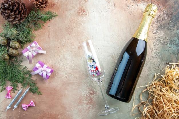 Vista superior de la botella de champán con pequeños regalos en la luz de regalo foto de navidad año nuevo alcohol de color