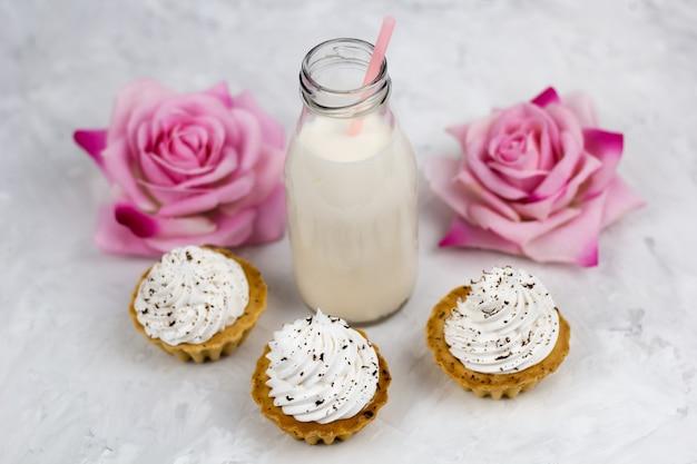 Vista superior botella de leche, rosas, cupcakes dulces, fondo claro de hormigón