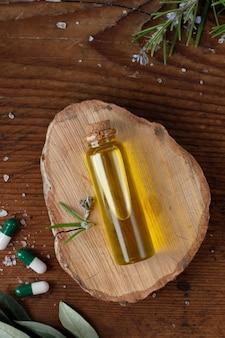 Vista superior botella de plástico con aceite y cápsulas sobre la mesa