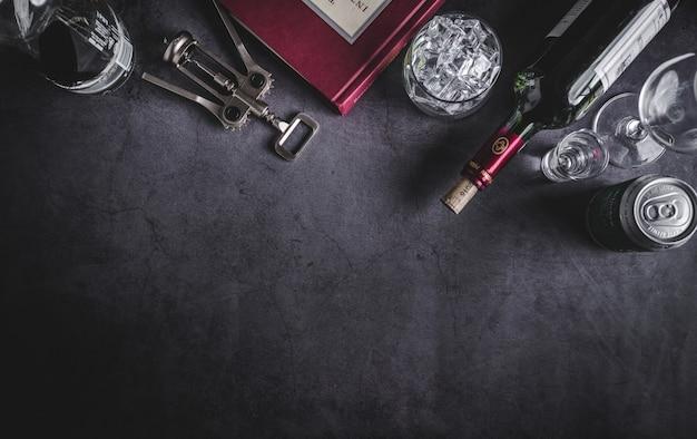 Vista superior de la botella de vino, botella de vodka, cubito de hielo, cerveza y sacacorchos