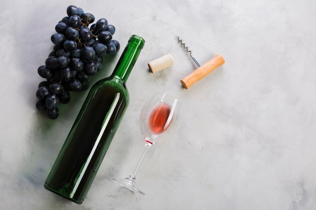 Vista superior botella de vino tinto y uvas
