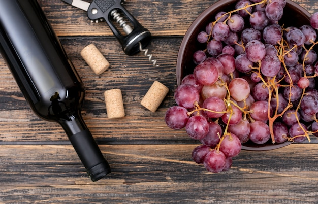 Vista superior botella de vino con uva en un tazón en horizontal de madera oscura