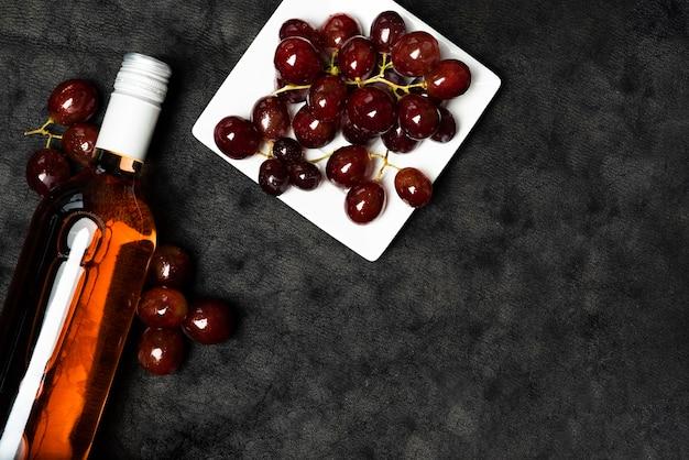 Vista superior botella de vino con uvas