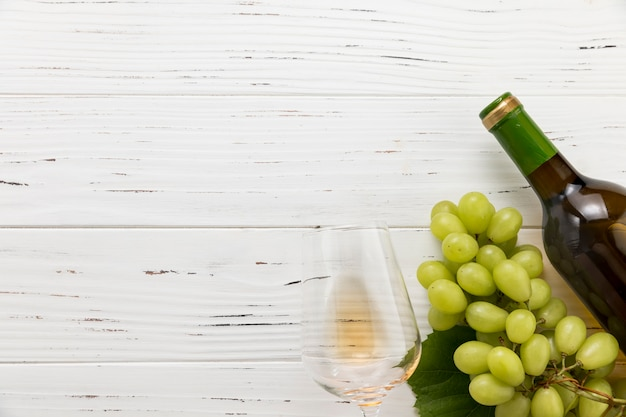 Vista superior botella de vino con vaso y racimo de uvas