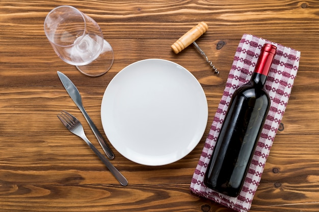 Vista superior botella de vino con vaso sobre fondo de madera