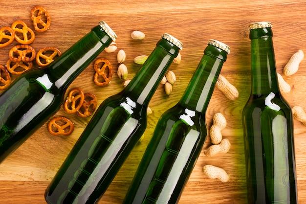 Vista superior de botellas de cerveza con aperitivos